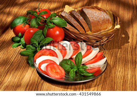 Mozzarella, tomatoes, basil, bread, composition on a wooden table - stock photo