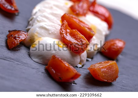 mozzarella with fried tomatos on black stones plates.  caprese salad  - stock photo