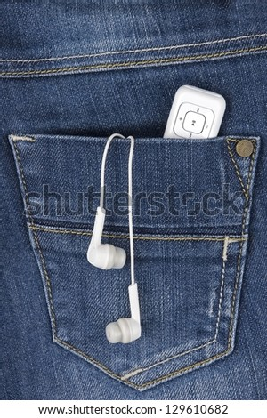 MP3 player and earphones sticking out of jeans pocket - stock photo