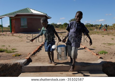 MPHANDULA, MALAWI – CIRCA MAY 2007 : Loal kids carry water can in 'Raising Malawi' orphanage circa May 2007 in Mphandula. The orphanage is a charity non-profit organisation, co-founded by Madonna. - stock photo