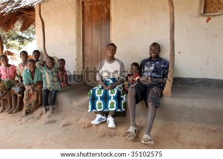 MPHANDULA, MALAWI – CIRCA MAY 2007 : Yohan David (R) relaxes in front of a house May 2007 in Mphandula, Malawi. David's son was adopted by singer Madonna. - stock photo