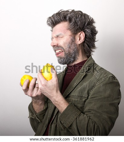 Mr. IceMan, smiling man with a beard, beard covered with hoarfrost, man holding lemon, he stares at them. fashion man in knitted sweater and jacket.  - stock photo