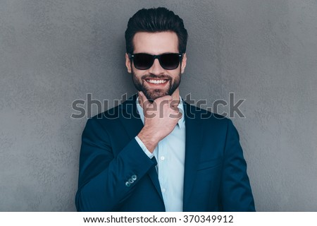Mr. Perfect Smile. Close-up of cheerful young handsome man in sunglasses keeping hand on chin and looking at camera with smile while standing against grey background - stock photo