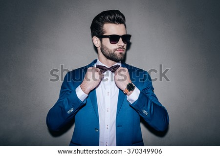 Mr. Perfection. Close-up of handsome young man wearing sunglasses adjusting his bow tie and looking away while standing against grey background - stock photo