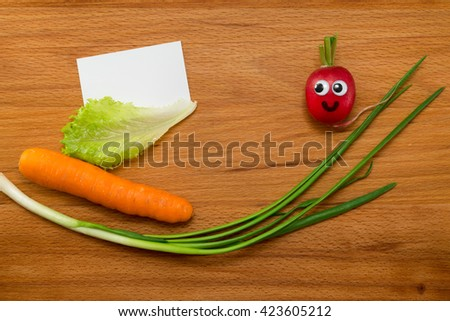 Mr. Radish is smiling and looking at the blank card, next are the onion, lettuce and carrot on wooden table. Close-up view from above - stock photo