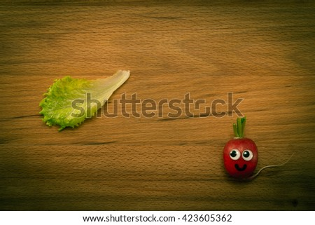 Mr. Radish is smiling and looking at the lettuce on wooden table. Close-up view from above, image vignetting and the yellow-green toning - stock photo
