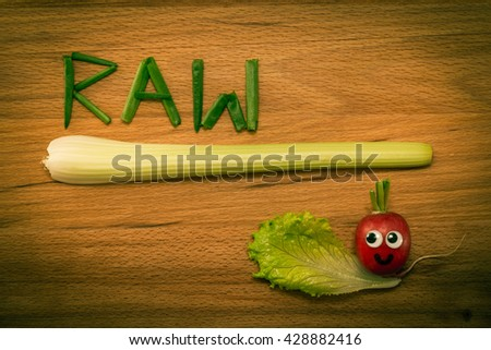 Mr. Radish is smiling and looking at the onion petals folded in the form of the word 'RAW' and celery on wooden table. Close-up view from above, image vignetting and the yellow-green toning - stock photo