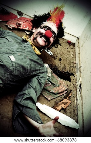 Mr Sleepy The Creepy Clown Lays On A Holey Rubbish Littered Floor With A Horrific Smile Across His Frightening Face - stock photo