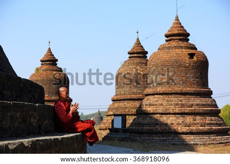 MRAUK U, MYANMAR -JAN 17: Unidentified Buddhism  buddhist monk meditating peacefully in Ratanabon temple on January 17, 2016 in Mrauk U, Myanmar. Southeast Asian monk in a Buddihist temple - stock photo