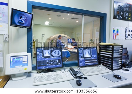 MRI machine and screens with doctor and nurse - stock photo