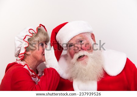 Mrs Claus whispers a secret into Santa's ear.  Perhaps she knows who has been naughty or nice. - stock photo