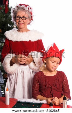 Mrs. Santa Claus looks on with satisfaction as a young girl finishes working on a Christmas craft project of decorating a stocking