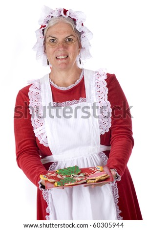 Mrs. Santa offering the viewer a plateful of decorated Christmas cookies,.  Isolated on white. - stock photo