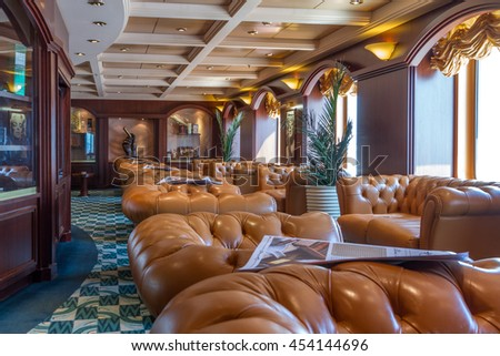 MSC cruise liner - JULY 4, 2016: Luxurious english cigar room with leather armchairs and wooden round table. - stock photo