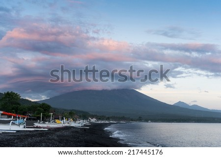 Mt. Agung, Bali, Indonesia. Mt. Agung, an active volcano, as seen from the Amed area od eastern Bali. Traditional fishing boats line the black sand beach as they return to shore in the morning. - stock photo