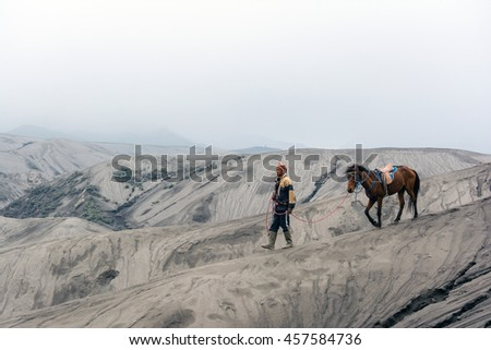 Mt. Bromo , East Java, Indonesia. May 21, 2016. A horseman walking his horse on sand dune after providing horseback riding services to tourist at Bromo-Tengger-Semeru National Park, a nature reserve.