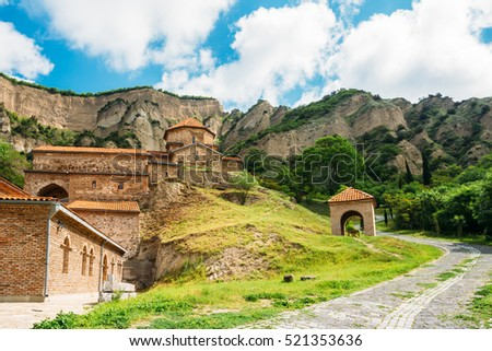 Mtskheta, Georgia. The Picturesque View Of Shiomgvime Or Shio-Mgvime Monastery, Medieval Monastic Complex In Limestone Canyon In Sunny Summer Spring Day Under Cloudy Sky.