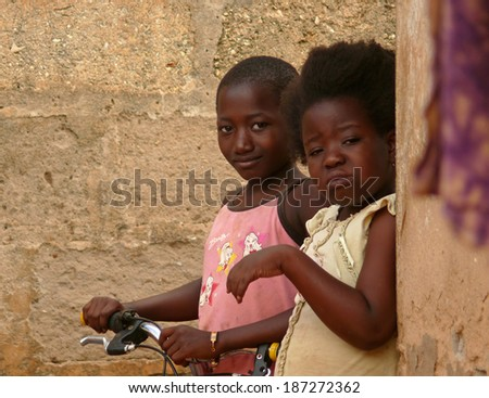 MTWARA, Tanzania - December 3, 2008: the Village. Strange girl peeking out from behind the wall. The wall of a residential house in Mtwara, Tanzania, December 3, 2008