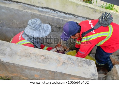 "Muadzam Shah, Malaysia - March 22, 2018: Municipal workers ""Alam Flora"" uses sweepers and shovels to clean the garbage in the drain and put into the garbage bag."