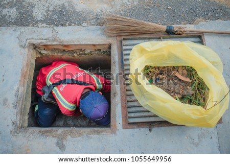"Muadzam Shah, Malaysia - March 22nd, 2018: Municipal worker ""Alam Flora"" uses sweepers and shovels to clean the garbage in the drain and put into the garbage bag."