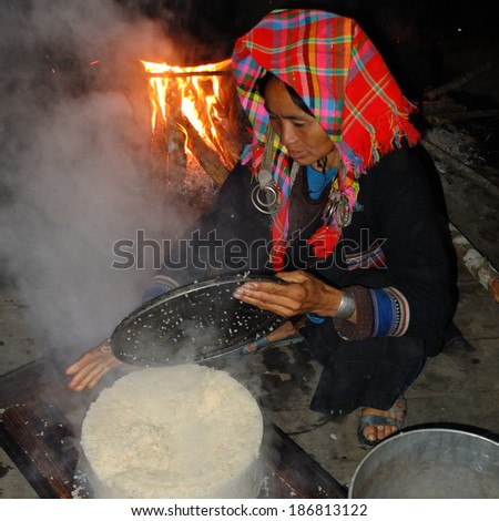 MUANG KHUA, LAOS -  FEBRUARY 2:  An Akha woman wearing traditional clothes is cooking rice at home, on February 2, 2014, in Muang Khua, Laos.  - stock photo