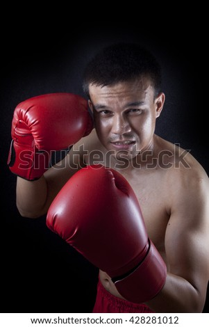 muay thai boxer man trainings. studio shot on black background