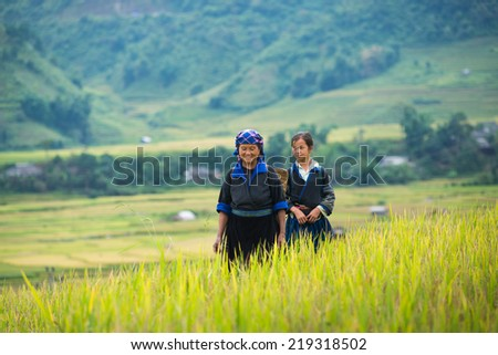 MUCANGCHAI, VIETNAM, SEPT 20: Unidentified H'mong ethnic minority woman with her granddaughter on September 20, 2014 in Mucangchai, Vietnam. H'mong is the 8th largest ethnic group in Vietnam.