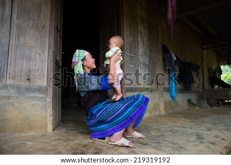 MUCANGCHAI, VIETNAM, SEPT 15: Unidentified H'mong ethnic minority woman with her son on September 15, 2014 in Mucangchai, Vietnam. H'mong is the 8th largest ethnic group in Vietnam.