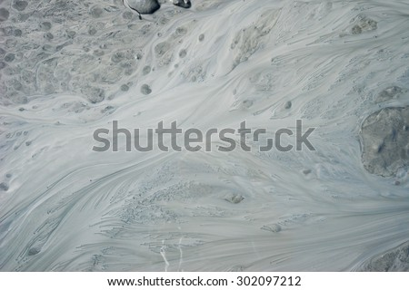 Mud and soil flow in stream leaving silt pattern. - stock photo