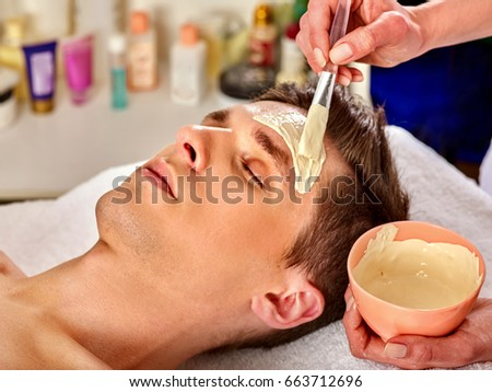Mud facial mask of man in spa salon. Healing massage with clay full face. Male lying spa bed. Beautician with bowl therapeutic procedure us anti-aging cosmetic .