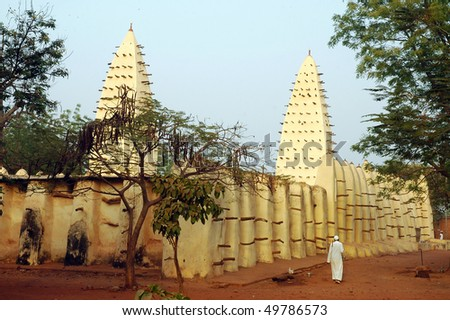 Mud mosque at Bobo Dioulasso with muslim man - stock photo