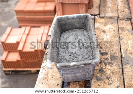 Mud pan with cement and mortar for bricklaying on construction site  - stock photo