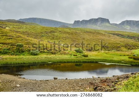 Muddy pond in the Scottish Highlands with the Cuillin Hills in the background - stock photo