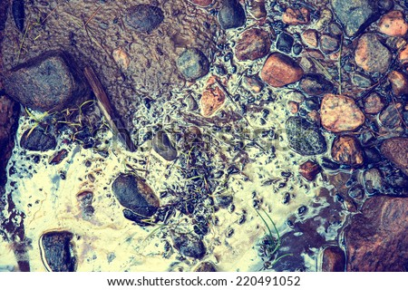 Muddy sand and stones at a beach contaminated with toxic chemical gasoline waste.  Small patches of grass grow around the stones.  Filtered for a retro, vintage look. - stock photo