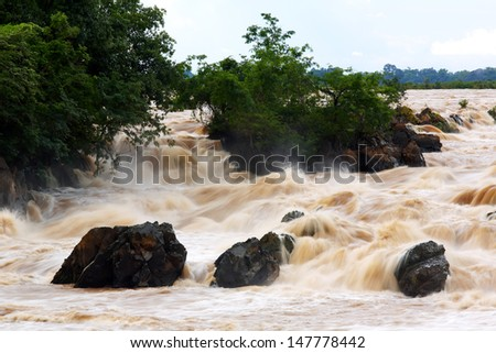 Muddy waterfall with rain at Somphamit Waterfall from Mekong River in Champasak Province, Laos - stock photo
