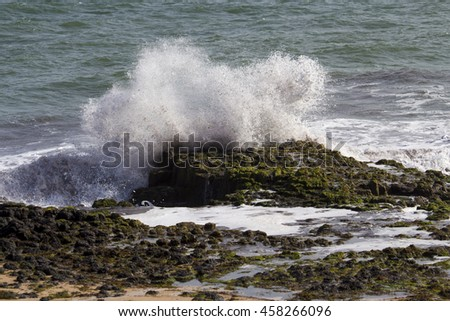 Muddy waves from the  Indian Ocean waves breaking on basalt rocks at  Ocean beach Bunbury Western Australia on a sunny morning in mid winter  sends salty spray high into the air. - stock photo