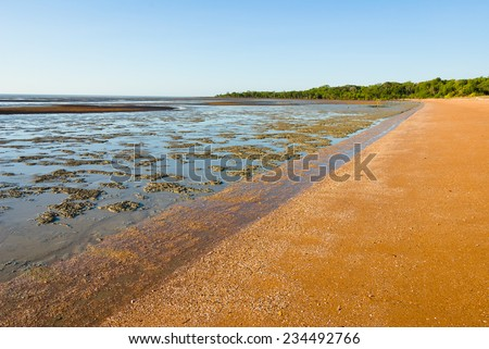 Mudflats beside a sandy beach exposed at low tide. Pocock's Beach, West Alligator Head, Kakadu, Northern Territory, Australia - stock photo