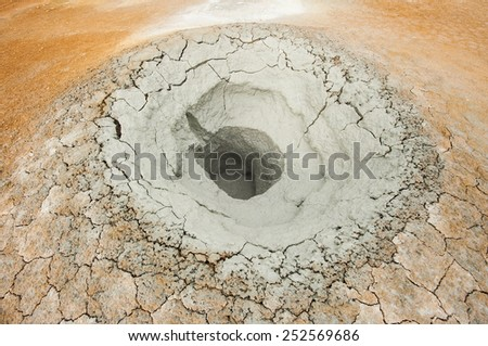 Mudpot in the geothermal area Hverir, Iceland. The area around the boiling mud is multicolored and cracked - stock photo