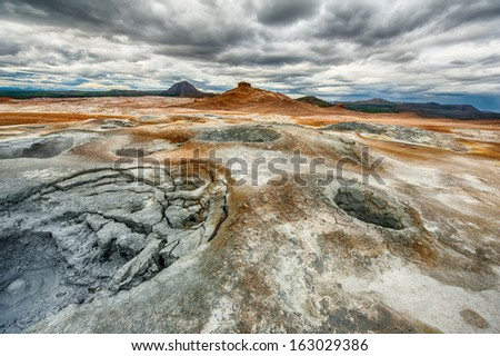 Mudpots in the geothermal area Hverir, Iceland. The area around the boiling mud is multicolored and cracked. HDR image - stock photo