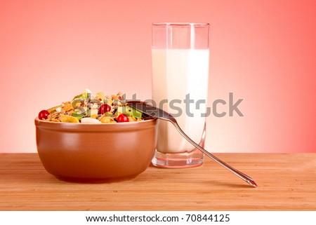 Muesli and milk on red background - stock photo