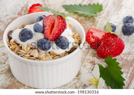 Muesli and yogurt with fresh berries. Selective focus - stock photo