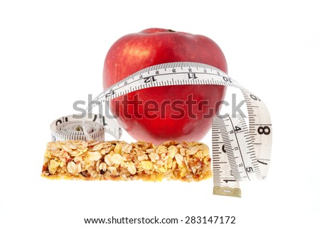 Muesli bar and red apple with measuring tape on white background  - stock photo