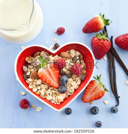 Muesli in heart-shaped bowl with fresh berries and milk - stock photo