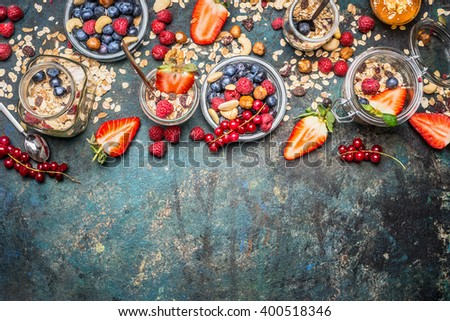 Muesli with fresh berries , nuts and seeds. Balanced breakfast ingredients on rustic background. Muesli breakfast in glass jars, top view, border.  Healthy lifestyle and diet food concept. - stock photo