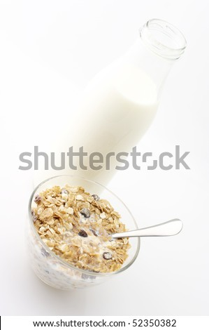 Muesli with milk in glass bowl and bottle of milk on white background. - stock photo