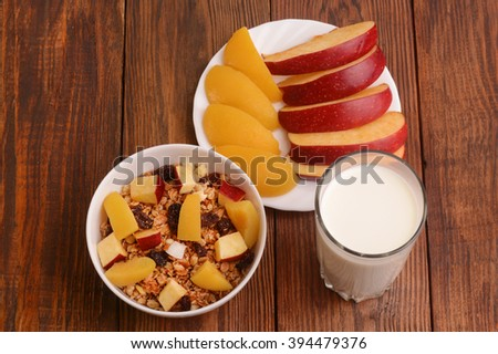 muesli with peach, apple and a glass of milk on wooden background