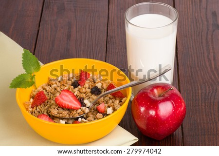 muesli with strawberries, apple and a glass of milk on a green napkin