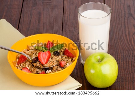 muesli with strawberries, apple and a glass of milk on wooden background - stock photo