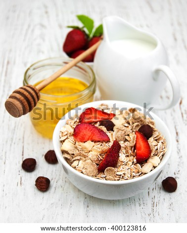 Muesli with strawberries on a old wooden background - stock photo