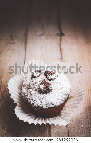 Muffin on a wooden table. Shallow depth of field.